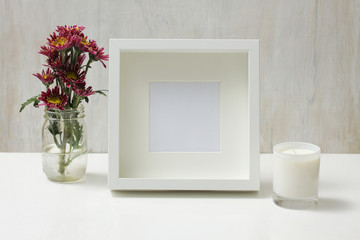 Blank picture frame with flowers and candle, home decor.