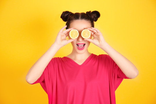 Beautiful young woman with lemon halves near eyes on yellow background
