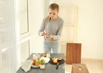 Young woman photographing food with smart phone