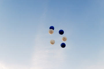 Helium balloons fly to the blue sky.