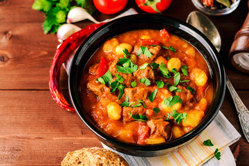 Goulash in ceramic bowl on wooden background. Traditional hungarian soup.