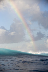 Rainbow over wave at sea, Tahiti, South Pacific