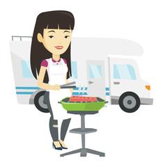 Woman having barbecue in front of camper van.
