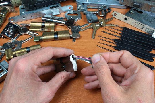 Locksmith inserts key in cylinder lock