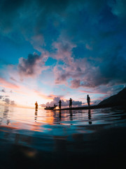 Silhouette of small group of people by waters edge at sunset, Tahiti, South Pacific