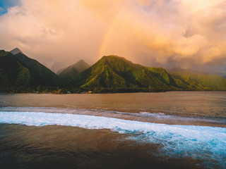 Island and coastline, rainbow coming through clouds, Teahupoo, Tahiti, South Pacific