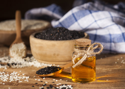 Fresh sesame oil in a glass bottle and white and black seeds in wooden bowls