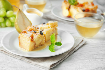Delicious bread pudding with fruits and tea on wooden table