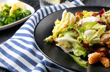 Plate with chicken salad on table