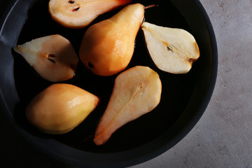 Pears with wine and spices in dish, closeup