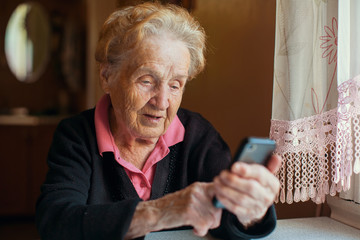 An old woman uses a smart phone.