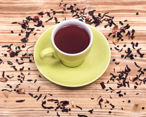 Wild berry tea in green cup with hibiscus leafs on wooden vintage background