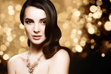 Fashion portrait of young caucasian model with gold jewelry on golden background. Beautiful brunette woman with long shiny hair. Glamour trendy accessories and hairstyle.