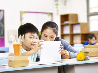 asian elementary school girl and schoolboy using tablet together