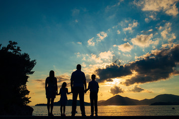 Silhouette of a family with children against the backdrop of the setting sun and sea in Montenegro.