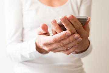 Close up of middle aged woman's hands holding smart phone (selective focus)