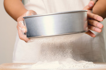 Sifting flour on wooden board,food ingredient,prepare for cooking or baking