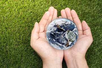 Hands holding earth on green grasses. Elements of this image furnished by NASA