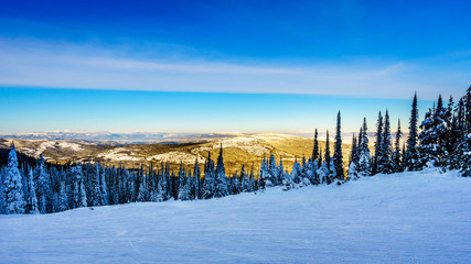 Wall Mural - Sunset over the snow covered hills surrounding the alpine ski village of Sun Peaks in the Shuswap Highlands of central British Columbia, Canada
