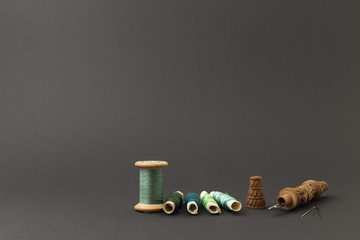 Different rolls with green polyester and silk thread, needles, and a wooden carved needle container with grey background