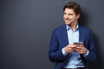 lächelnder mann hält sein mobiltelefon in den händen und schaut zur seite