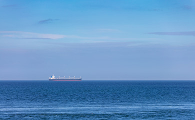 Large cargo tanker sailing across a blue sea horizon