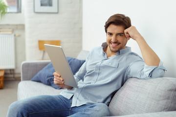 lächelnder mann sitzt auf dem sofa und hält ein tablet in der hand