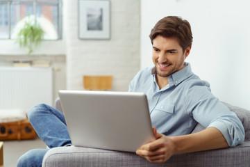 mann sitzt zuhause auf dem sofa und schaut auf seinen laptop