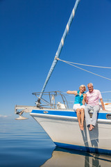 Happy Senior Couple Sitting on the Side of a Sail Boat
