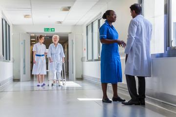 Nurse Helping Elderly Old Female Patient in Hospital Corridor with Doctor