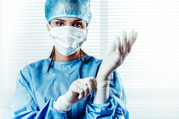 Female doctor Surgeon putting on surgical gloves