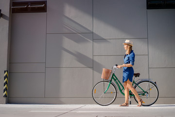 Cycling lifestyle. Pretty young woman in hat riding bicycle against grey wall.