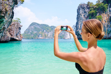 Tourism and vacation in Thailand. Pretty young woman taking picture of beautiful landscape on tropical beach. Focus on camera.