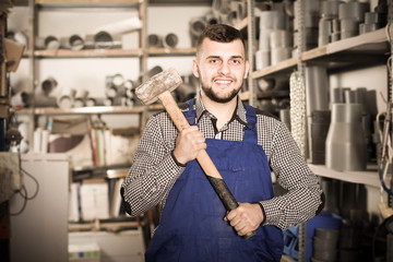 Smiling male builder showing constructing instruments