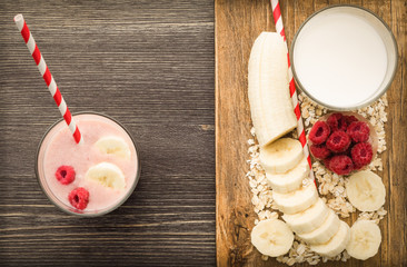 The concept of a healthy drink, ingredients for cocktails. Banana, raspberries, oatmeal, milk on a wooden board on a black wooden background