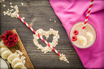 Love of smoothies. Delicious and healthy banana smoothie with raspberries in glass glasses on a napkin and black wooden background
