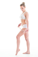 Slim young woman model with centimeter measuring her slim beautiful body. Isolated over white background