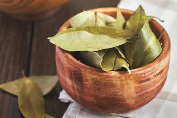 Dry bay leaves (Laurus nobilis) in wooden bowl