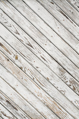 Old wooden gate is covered with shabby white paint. Texture. Oblique lines.