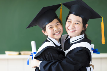 Two happy teenager in graduation gowns hugging and smiling .