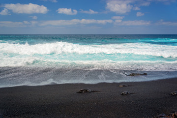Front view of waves on a black sand beach on Playa del Paso in Lanzarote, Canary Islands, Spain