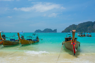 Beach with long tale taxi boats on island