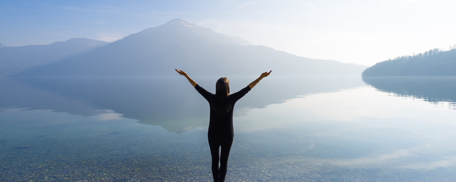 The joy of unity with nature. Woman with open arms by the lake on a background of mountains.