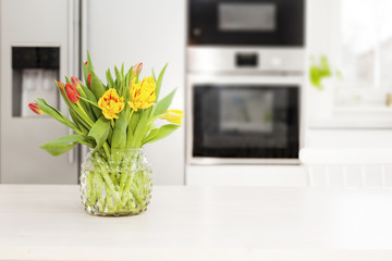 bunch of yellow and red tulips with unfocused background of a fancy kitchen