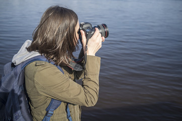Cute female photographer with camera in hands on background of river