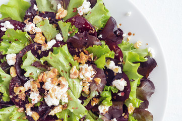 vegetable salad of lettuce leafs, sliced beetroot, feta cheese, and walnuts with olive oil and balsamic vinegar dressing