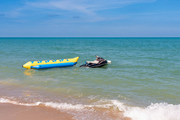 summer holiday by the sea. Beautiful bright blue water and red and white boat and yellow banana boat.