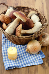 Basket with fresh penny bun  mushrooms on table