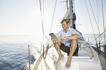 "Mediterranean Sea, ""Goldene Rente"", mature man using tablet computer on sailing boat"