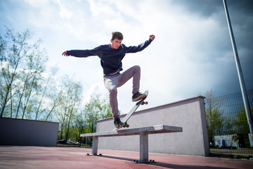 Skater doing blunt slide trick on bench in skatepark